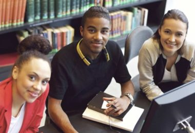 three 30-year-old college friends in library
