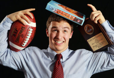 student with books and a football ball