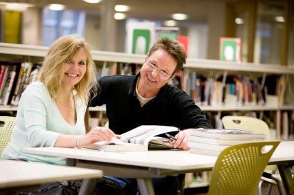 two 40-year old students studying in library